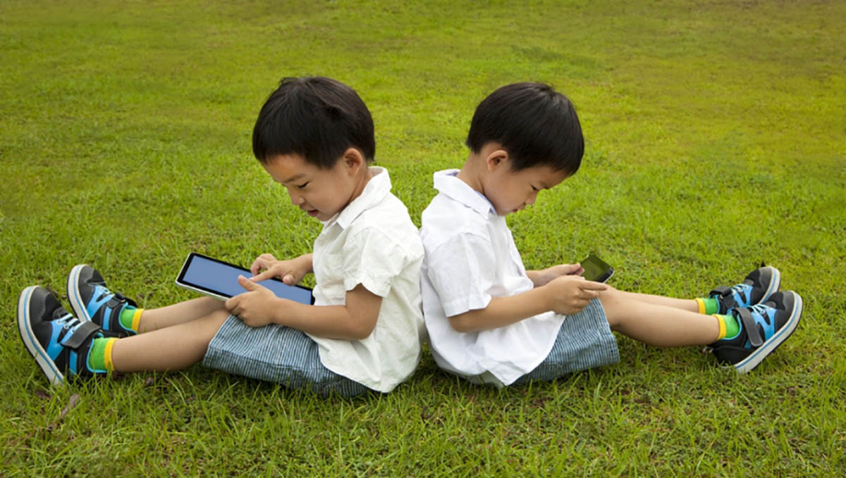 Kids with phones on the grass